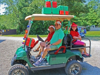 People in golf cart decorated with Christmas decorations