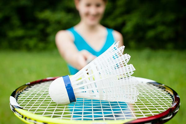 smiling girl holding a shuttlecock on a badminton racquet